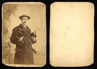 Man Holding Two Roosters Heavy Gloves in His Pocket Cabinet Photo